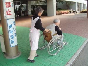 車椅子を押して外来へ案内